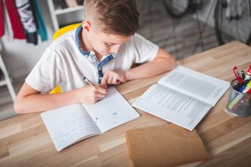 Focused preteen boy doing homework on desk in his room