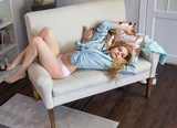 Beautiful young woman in underwear lying on white sofa dreaming. - 207969920