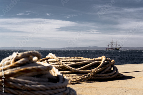 Fotobehang Beige Old wooden sailboat with three masts anchored offshore, waiting for the storm to calm down. In the front lie a pair of long ropes on the ground.