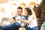 Happy couple watching a smart phone sitting on a bench - 207975350