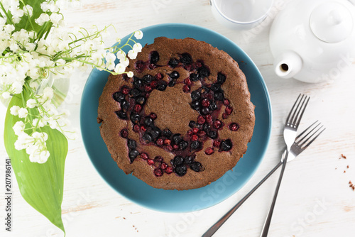 Healthy homemade dessert. Traditional Siberian cake with bird cherry, cowberry and black currant served with white teapot and lily of the valley flowers on white background