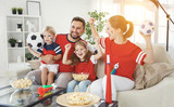 family of fans watching a football match on TV at home - 207987593