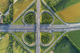 Cloverleaf interchange seen from above. Aerial view of highway road junction in the countryside with trees and cultivated fields. Bird's eye view.