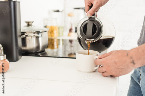 partial view of man pouring coffee into cup from coffee maker at kitchen