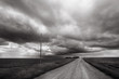 Storm blows through rural Alberta countryside; black and white image of prairie storm with gravel road leading to horizon