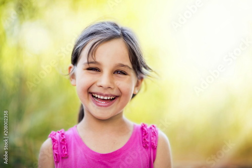 Foto Murales Close up Portrait of Happy Smiling Child Girl Outdoors in Summer