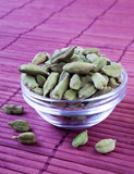 Cardamom Pods in clear bowl on red mat - 208006374
