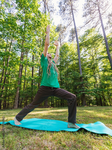 Fotobehang School de yoga Man in a yoga pose outside in a field surrounded by forest