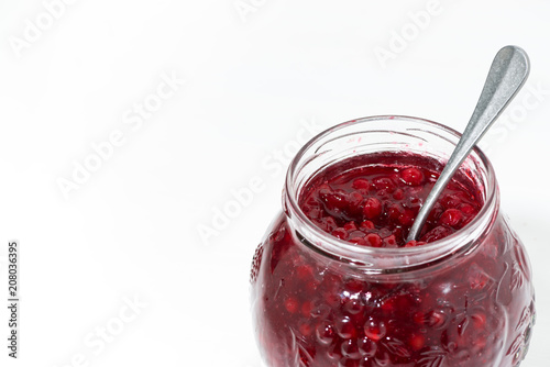 Sticker jar with sweet cowberry jam on white background