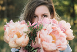 Florist woman looking over peony flowers