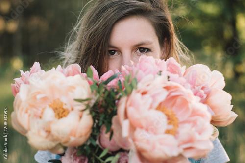 Foto Murales Florist woman looking over peony flowers