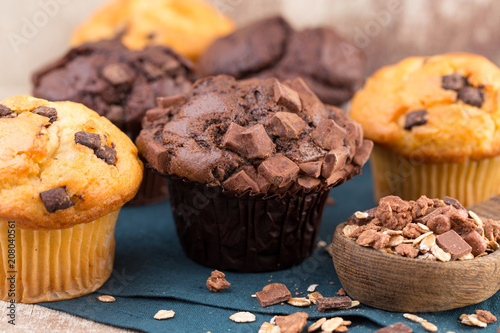 Wall mural Homemade muffins with chocolate, vintage background.