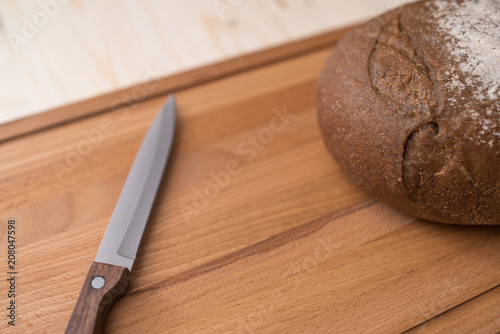 Fresh bread covered with flour on wooden board with knife closeup