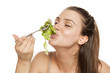 young happy woman eating lettuce salad on a white background