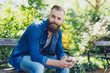 Attractive bearded man siting on a park bench