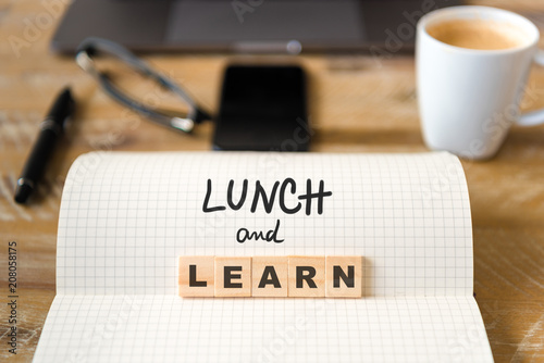 Closeup on notebook over wood table background, focus on wooden blocks with letters making Lunch and Learn text - 208058175