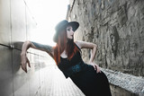 Creative redhead woman in gothic black dress and hat in the city. Street style - 208059934