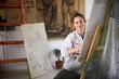 Leinwanddruck Bild - Artistic girl sitting in studio and paint on easel.