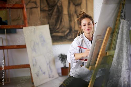 Leinwanddruck Bild Artistic girl sitting in studio and paint on easel.