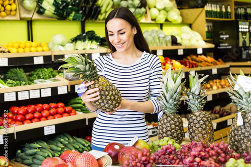 Attractive smiling young girl in casual clothes selects fruits and vegetables from a shelf in a grocery store.