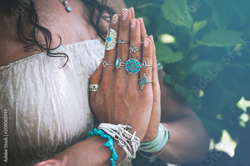 Fotobehang School de yoga close up of yoga woman hands in namaste gesture with lot of boho style jewelry rings and bracelets outdoor