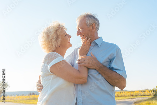Leinwanddruck Bild Low-angle view of a romantic elderly couple enjoying health and nature while standing together on a field in a sunny day of summer