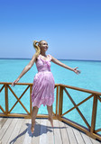 Young beautiful girl jumps in pink sundress on platform of villa on water under umbrella, Maldives.. - 208079125