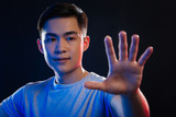 Transparent technology. Pleasant Asian man stretching out his hand while touching the transparent screen - 208085155