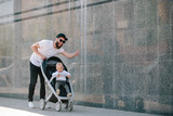 Father walking with a stroller and a baby in the city streets - 208086556