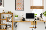Real photo of a desk with a computer screen, lamp and ornaments standing with a chair next to a shelf with more ornaments in a work room with posters on a wall and window with blinds - 208099942