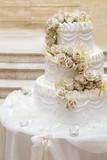 Torta elegantemente decorata con rose sopra un tavolo bianco - 208107782