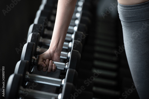 Sticker Attractive young sports woman lifting weights in the gym ,bodybuilding and loose weight concept