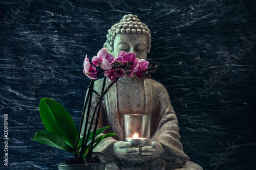 Fotobehang Boeddha Buddha statue with candle in hands and pink orchid flower ahead