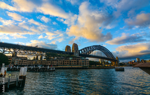 Fotobehang Sydney Sunset and evening clouds over Sydney Harbour Bridge as seen from the docks at Circular Quay