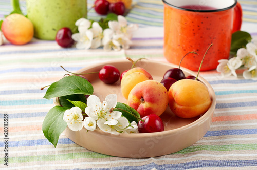Summer still life with berry tea, ripe apricots, juicy cherries and apple blossoms
