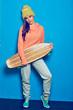 Full body portrait of sporty girl holding wooden skateboard, lon