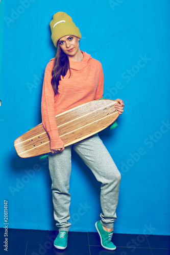 Aluminium Skateboard Full body portrait of sporty girl holding wooden skateboard, lon