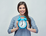 Young woman holding big blue alarm clock.