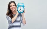 Smiling woman holding big alarm clock.