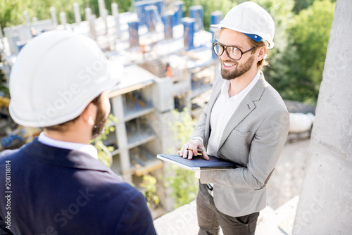 Two engineers or architects supervising the process of residential building construction standing on the structure outdoors