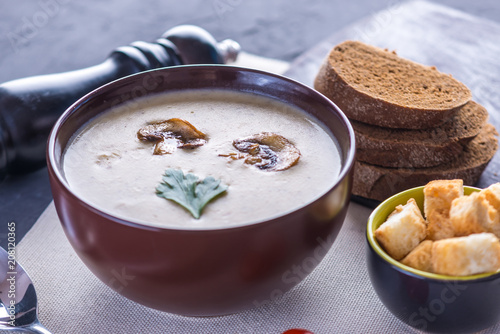 Mushroom cream soup in a brown plate on the table. Vegetarian traditional dish - 208120365