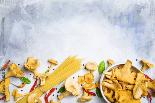 Foto Murales Ingredients for cooking pasta with mushrooms chanterelles in a creamy sauce, food background, top view