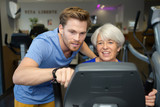 male trainer setting the elderly womans exercise machine