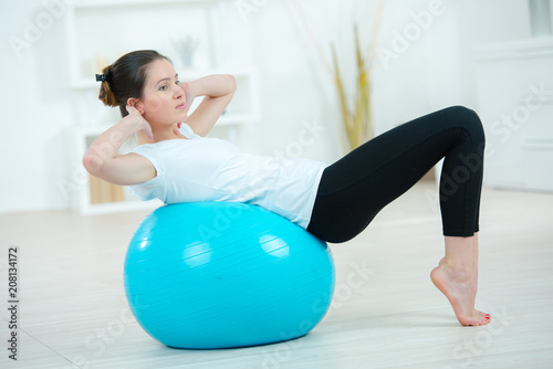 Plexiglas Fitness young woman exercising using a gym ball