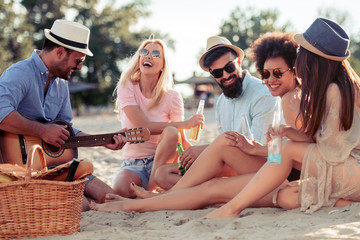 Group of friends with guitar having fun on the beach