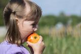 Little girl bites a ruddy apple - 208144328