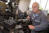 Senior worker using workshop equipment - 208144348