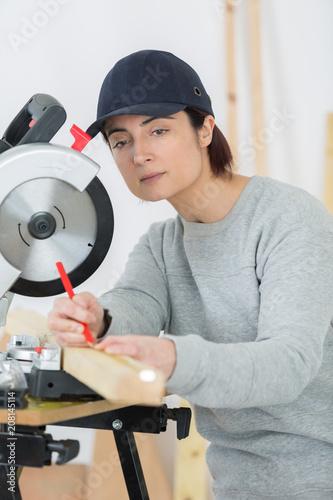 woman carpenter using circular saw - 208145114