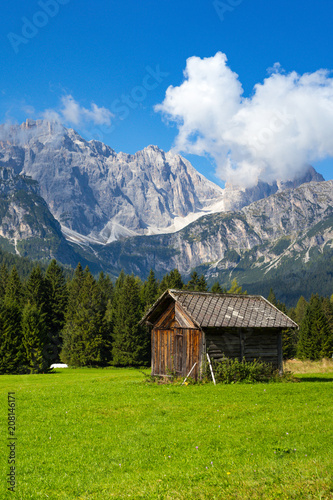 Foto Murales small wooden house in the mountains