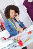 happy fashion designer talking phone in office - 208147184